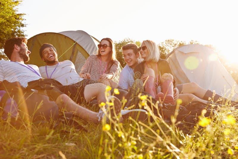 Grupo de amigos que se relajan fuera de las tiendas en acampada foto de archivo libre de regalías