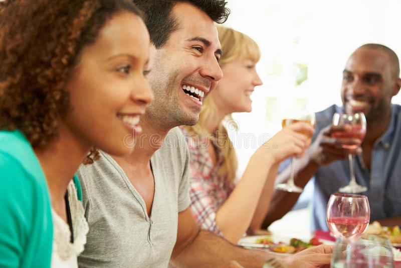Grupo de amigos que se sientan alrededor de la tabla que tiene partido de cena fotos de archivo libres de regalías