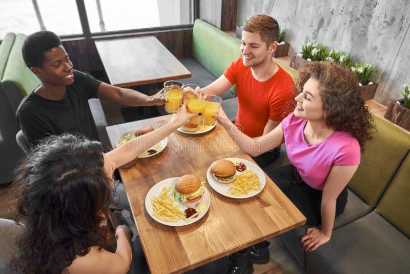 Grupo de amigos que se sientan en café en la tabla, vidrios que tintinean foto de archivo libre de regalías