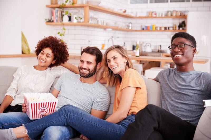 Grupo de amigos que se sientan en el hogar de Sofa And Watching Movie At mientras que come las palomitas imagenes de archivo