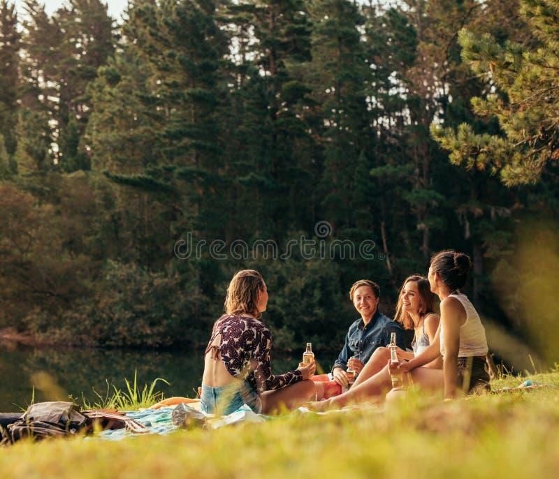 Grupo de amigos que se sientan en la parte posterior de una selección encima del coche fotografía de archivo libre de regalías