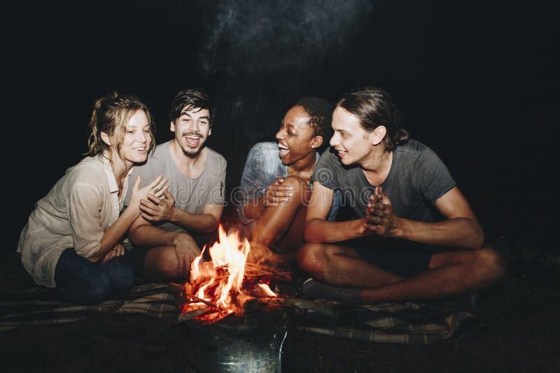 Grupo de amigos que sentam-se em torno de uma fogueira em um acampamento imagens de stock