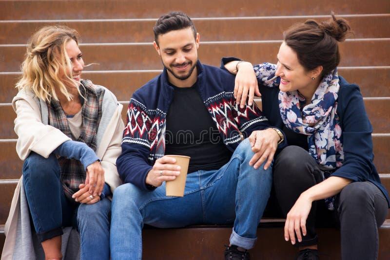 Grupo de amigos que sentam-se fora em escadas imagem de stock