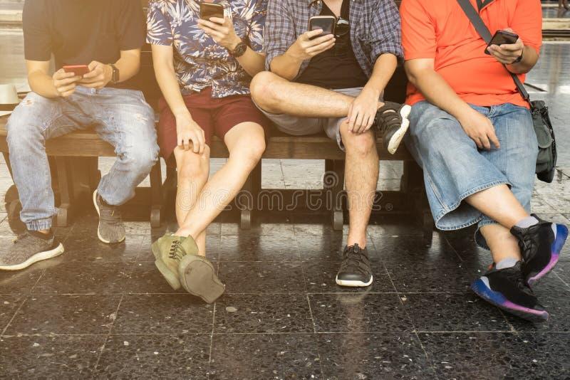 Grupo de amigos que sentam-se na cadeira e que usam o smartphone imagem de stock royalty free