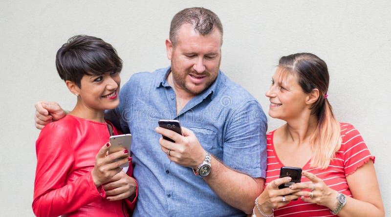 Grupo de amigos que sorriem e que olham o smartphone fotografia de stock