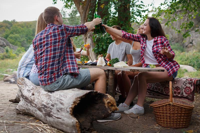 Grupo de amigos que têm o divertimento ao comer e ao beber em um piquenique - os povos felizes no BBQ party Tempo de verão feliz fotografia de stock