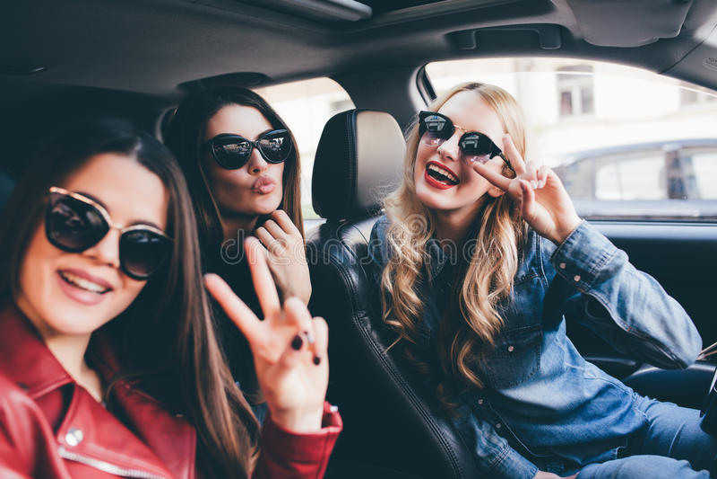 Grupo de amigos que têm o divertimento no carro Canto e riso na cidade fotos de stock royalty free