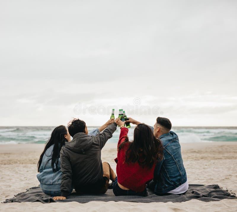 Grupo de amigos que têm o partido na praia imagem de stock