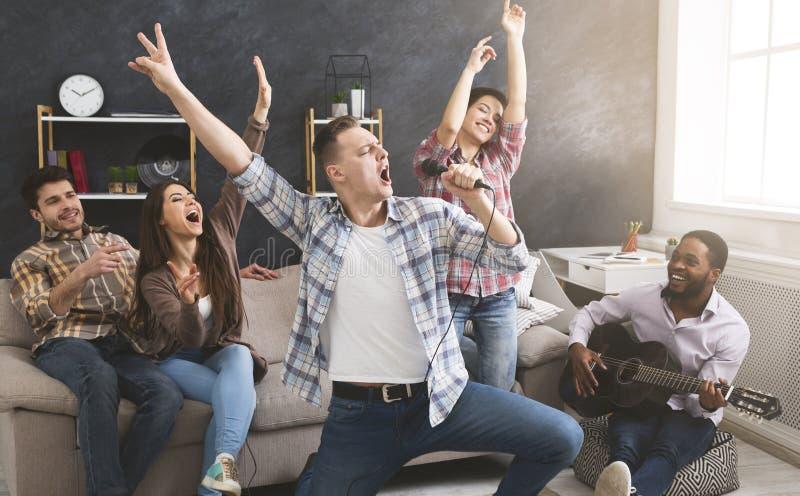 Grupo de amigos que têm um partido alegre em casa imagens de stock