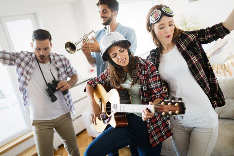 Grupo de amigos que tocan la guitarra y que van de fiesta en casa imagen de archivo libre de regalías