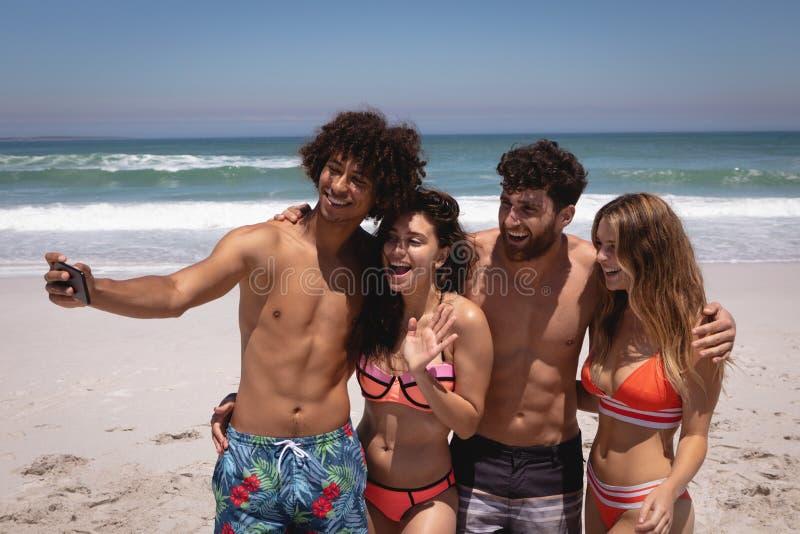 Grupo de amigos que tomam o selfie com telefone celular na praia na luz do sol fotos de stock