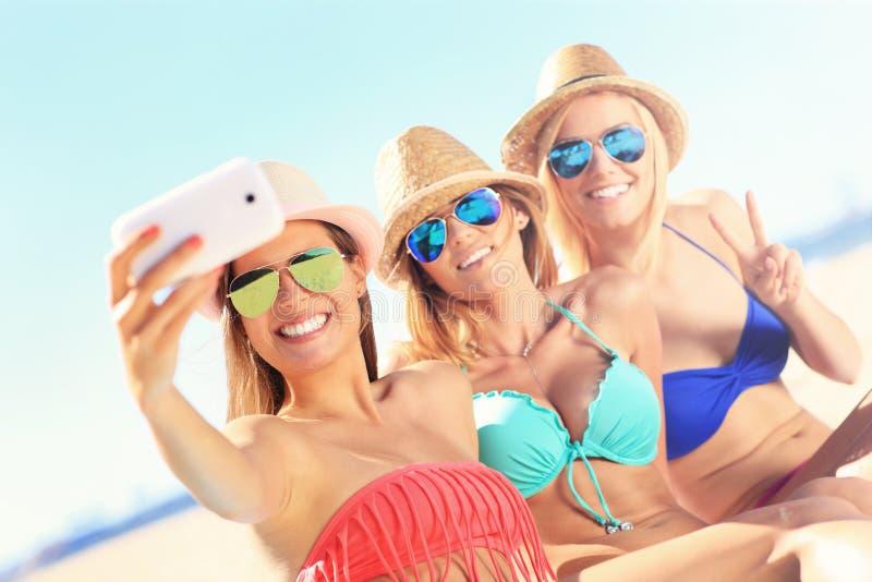 Grupo de amigos que tomam o selfie na praia imagens de stock royalty free