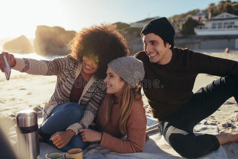 Grupo de amigos que tomam o selfie no partido da praia fotografia de stock royalty free