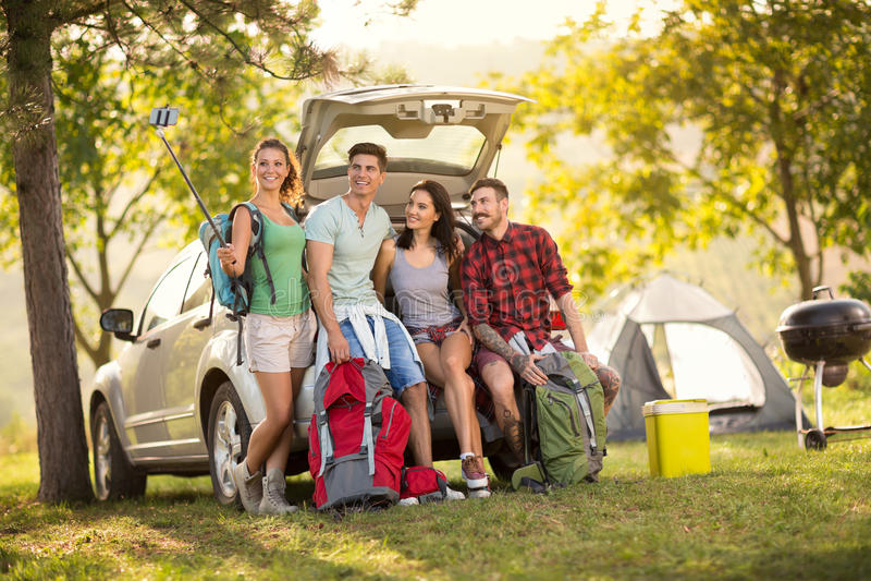 Grupo de amigos que toman el selfie con smartphone en acampada imágenes de archivo libres de regalías
