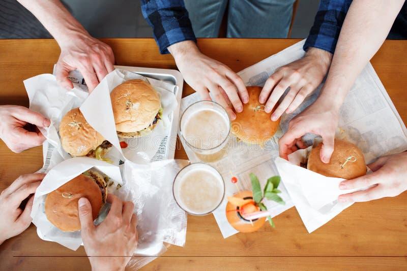 Grupo de amigos que tuestan los vidrios de cerveza y que comen en los alimentos de preparación rápida - gente feliz que va de fie fotografía de archivo
