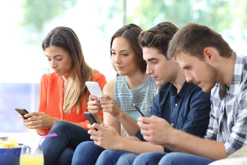 Grupo de amigos que usan sus teléfonos elegantes en casa imagenes de archivo