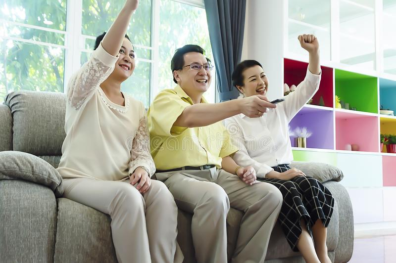 Grupo de amigos que ven la TV junto en casa el sentarse en el sofá cómodo fotografía de archivo