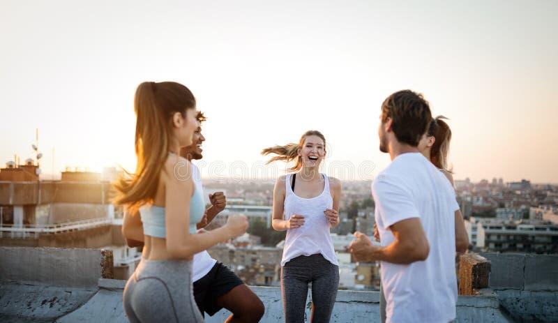 Grupo de amigos sanos aptos, gente que ejercita junto al aire libre en tejado fotografía de archivo