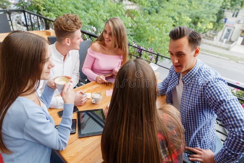 Grupo de amigos sonrientes con las tabletas y los teléfonos, relajándose en un fondo borroso Concepto de la vida del estudiante foto de archivo libre de regalías