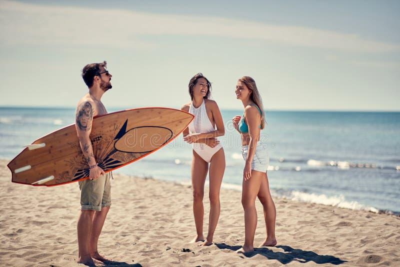 Grupo de amigos sonrientes que van a practicar surf en el peopl deportivo de la playa imagen de archivo libre de regalías