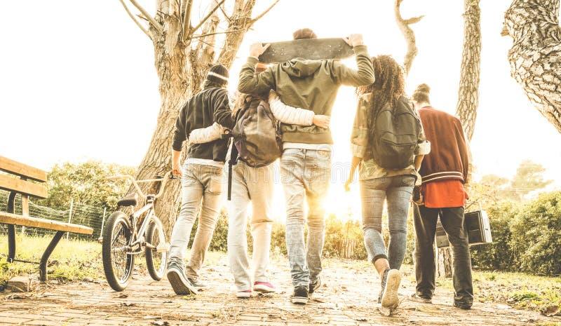 Grupo de amigos urbanos que caminan en parque del patín de la ciudad con el contraluz fotos de archivo libres de regalías