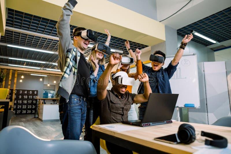 Grupo de apoyo de hombres de negocios multirraciales diversos jovenes que llevan gafas del vr que celebra su victoria en creativo imagen de archivo libre de regalías