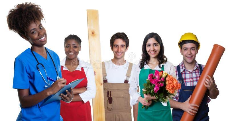 Grupo de aprendizes árabes e latin e caucasianos com a enfermeira afro-americano feliz foto de stock royalty free