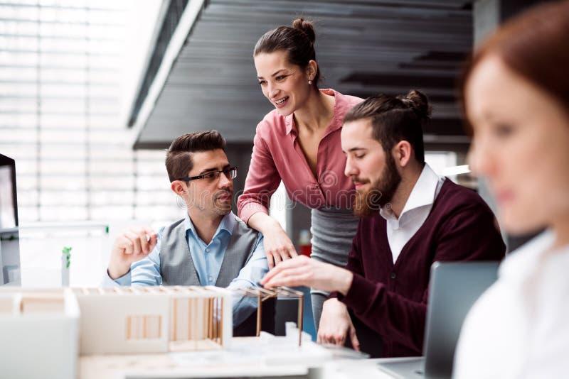 Grupo de arquitetos novos com o modelo de uma casa que trabalha no escritório, falando imagens de stock