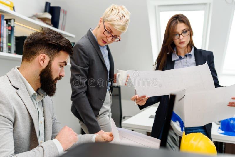 Grupo de arquitetos novos que trabalham em seu estúdio do escritório imagens de stock