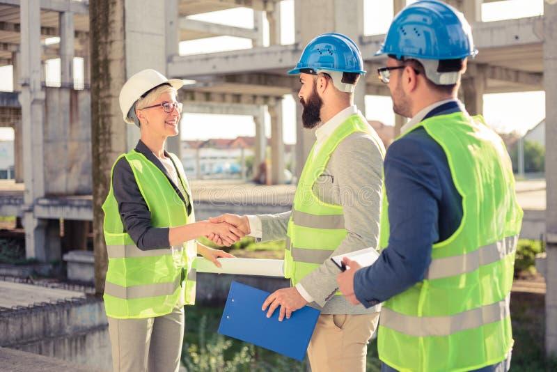 Grupo de arquitetos ou de sócios comerciais que agitam as mãos em um canteiro de obras imagens de stock