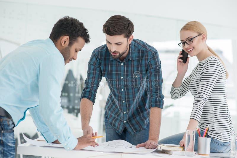 Grupo de arquitetos que discutem planos no escritório moderno fotografia de stock