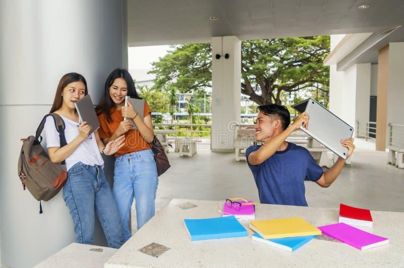 Grupo de asiático novo que estuda na universidade que joga o colo dos estudantes fotos de stock royalty free