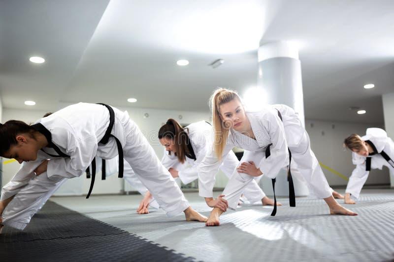 Grupo de atletas del Taekwondo que estiran y que entrenan así como su amigo físicamente discapacitado imágenes de archivo libres de regalías