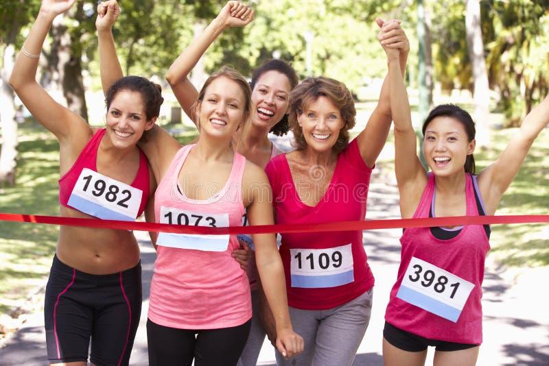 Grupo de atletas fêmeas que terminam a raça de maratona da caridade imagens de stock