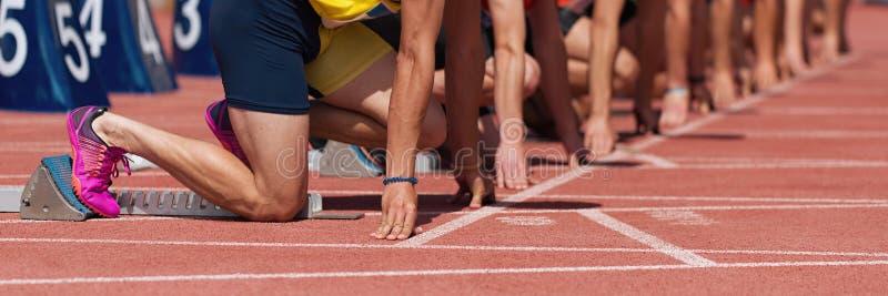 Grupo de atletas de pista de sexo masculino en bloques el comenzar fotos de archivo