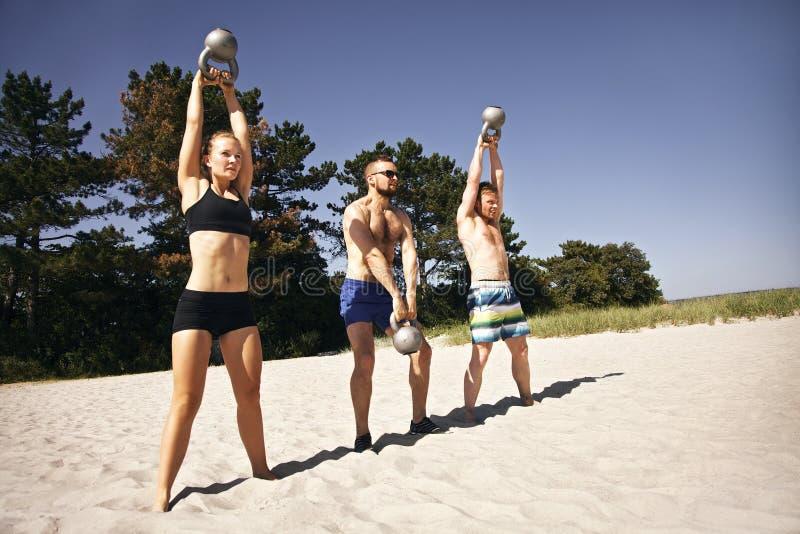 Grupo de atletas que se resuelven con la campana de la caldera en la playa imágenes de archivo libres de regalías