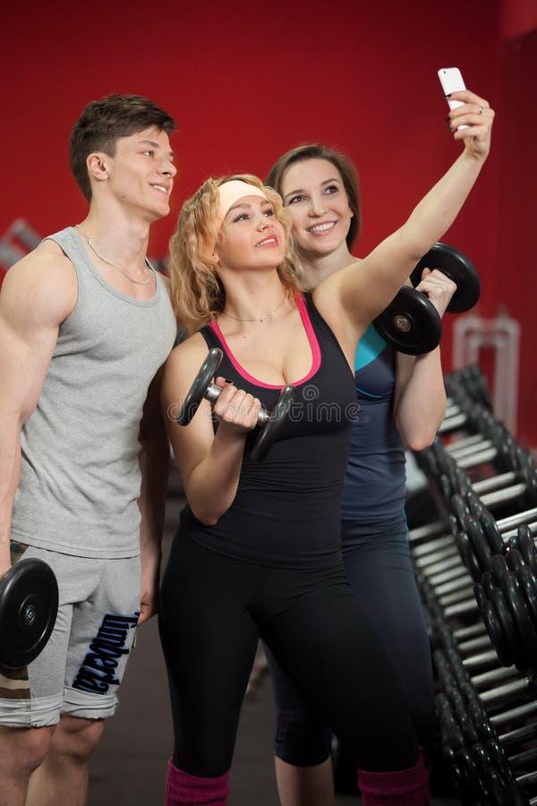 Grupo de atletas que toman el selfie con pesas de gimnasia en centro de aptitud fotos de archivo