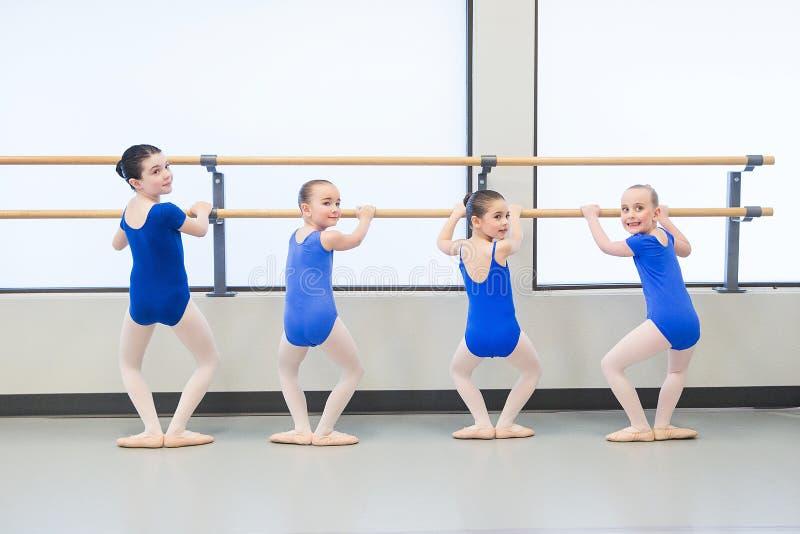 Grupo de bailarinas da criança que aprendem equilibrar na barra fotos de stock