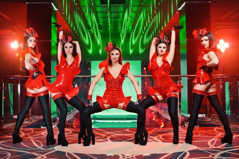 Grupo de bailarines de sexo femenino atractivos en la ejecución a juego roja de los equipos fotos de archivo libres de regalías