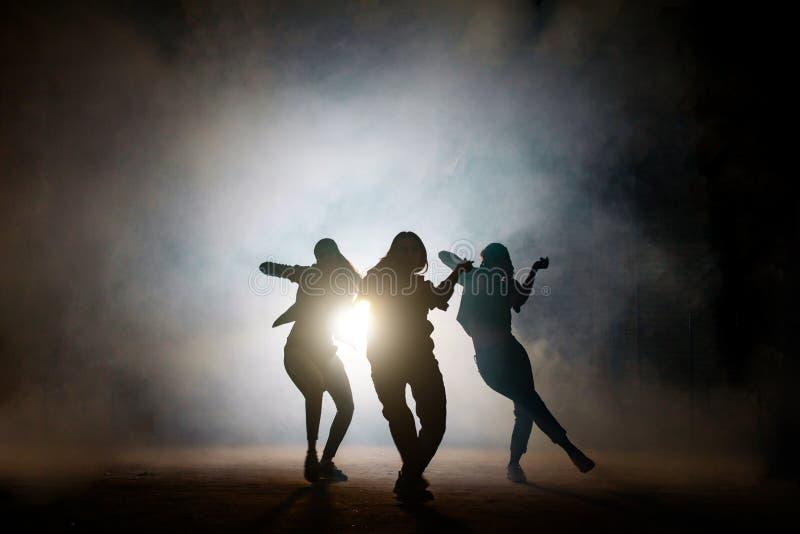 Grupo de bailarines de sexo femenino jovenes en la calle en la noche fotografía de archivo libre de regalías