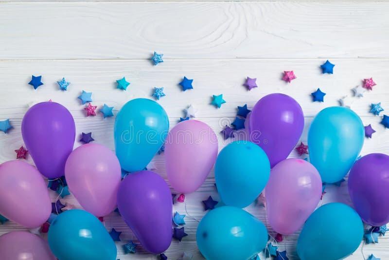 Grupo de balões coloridos do partido com as estrelas de papel no fundo de madeira branco foto de stock