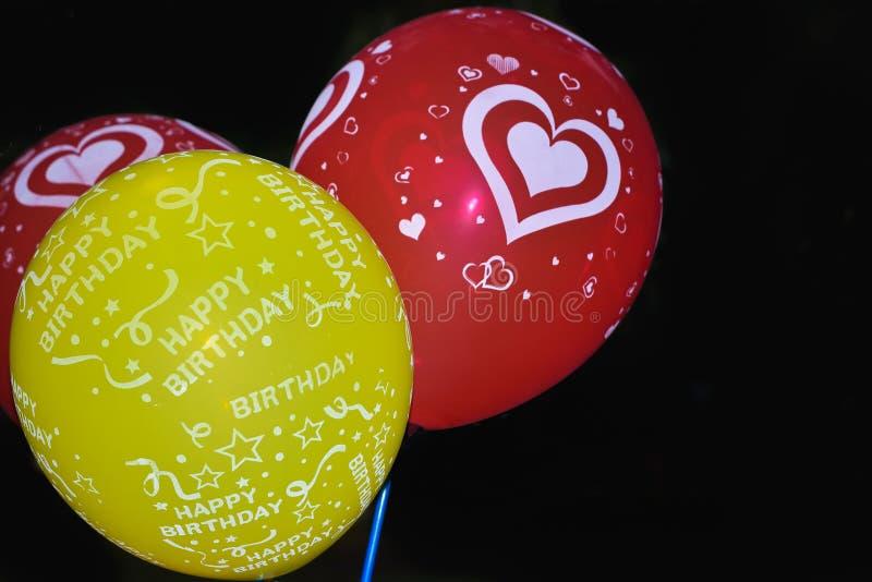Grupo de balões do voo da cor vermelha do verde cor-de-rosa Balão de voo do hélio do aniversário Isolado no fundo preto Celebraçõ fotografia de stock