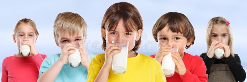 Grupo de bandera sana de cristal de la consumición de los niños de la leche de consumo del muchacho de la muchacha de los niños imagenes de archivo