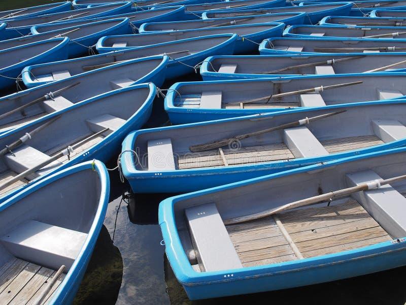 Grupo de barco a remos azul no rio fotografia de stock