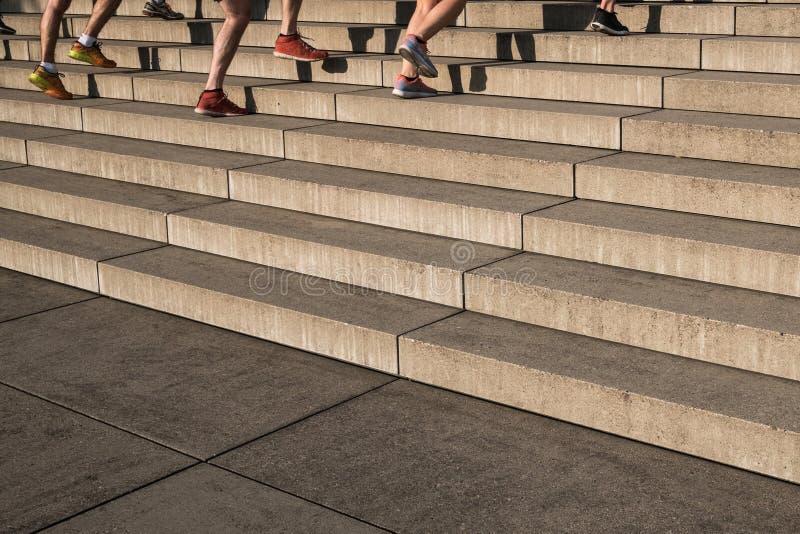 Grupo de basculador que funciona con las escaleras ascendentes - trainin al aire libre de la aptitud foto de archivo libre de regalías