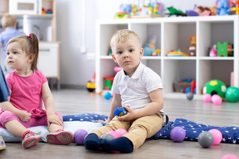 Grupo de bebés que juegan en guardería imagenes de archivo