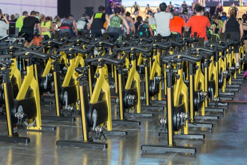 Grupo de bicis de giro amarillas modernas: Entrenamiento de la aptitud en clase en el gimnasio fotos de archivo