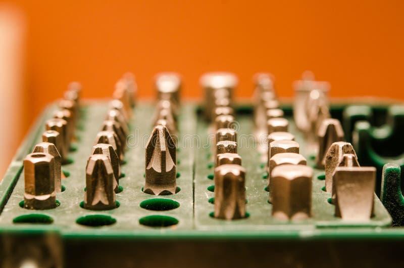 Grupo de bocados para a chave de fenda em uma caixa verde em um backgrou alaranjado imagem de stock