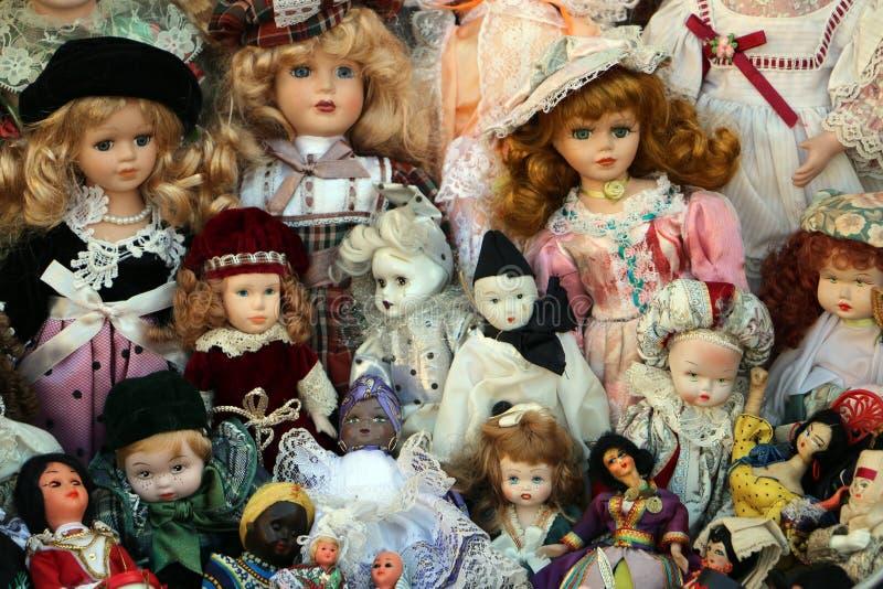 Grupo de bonecas velhas diferentes no mercado de coisas velhas, venda de garagem imagem de stock