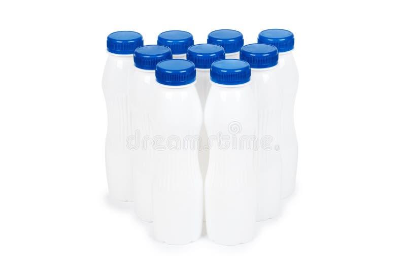 Grupo de botellas plásticas blancas con el yogur o la leche de la bebida Aislado en el fondo blanco Plantilla de la mercancía del imagen de archivo